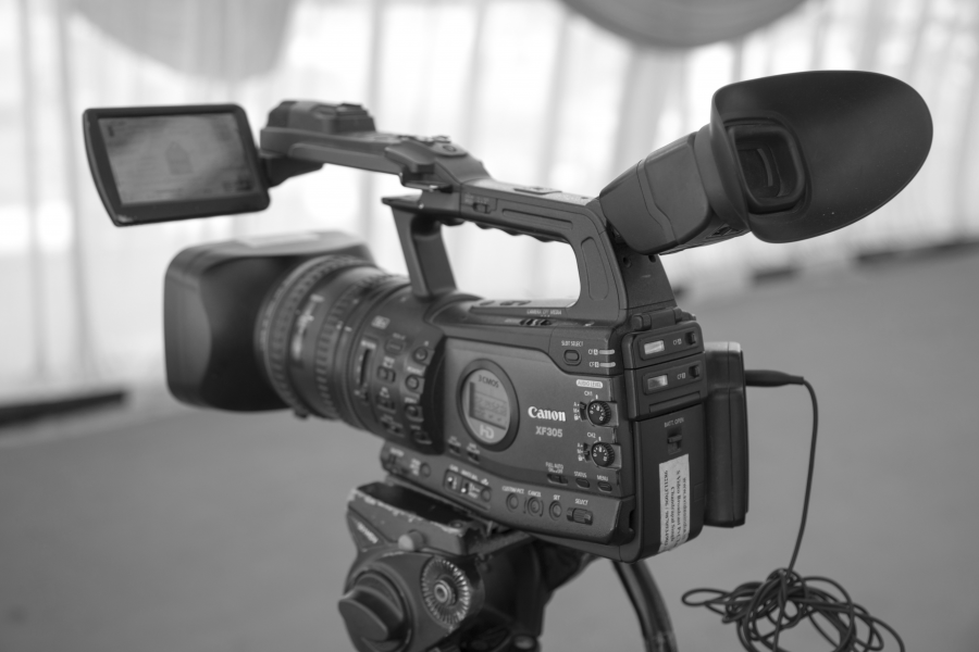 Black and white image of a professional video camera on a tripod