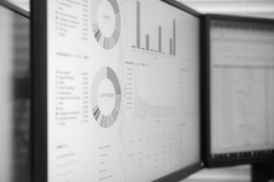 Black and white photo of 2 computer monitors displaying charts and graphs