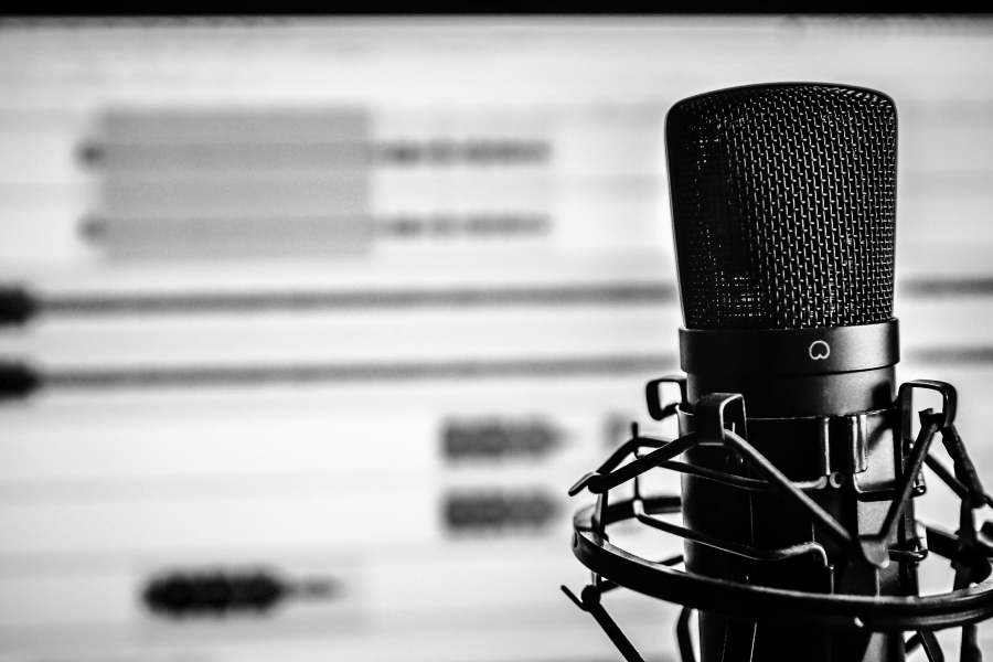 Black and White photo of a microphone in front of a computer monitor showing audio editing software