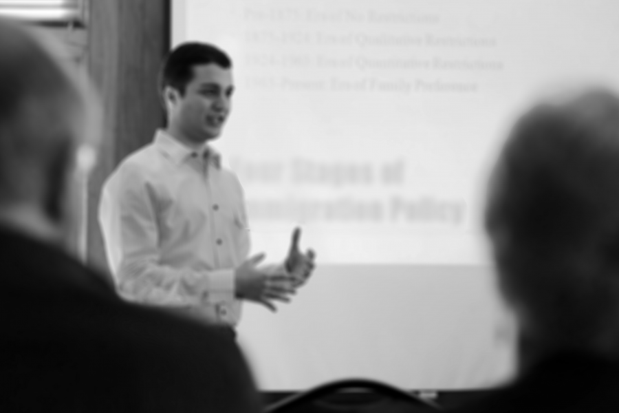 Black and White photo of an undergraduate giving a presentation with slideshow at a UW-Madison symposium