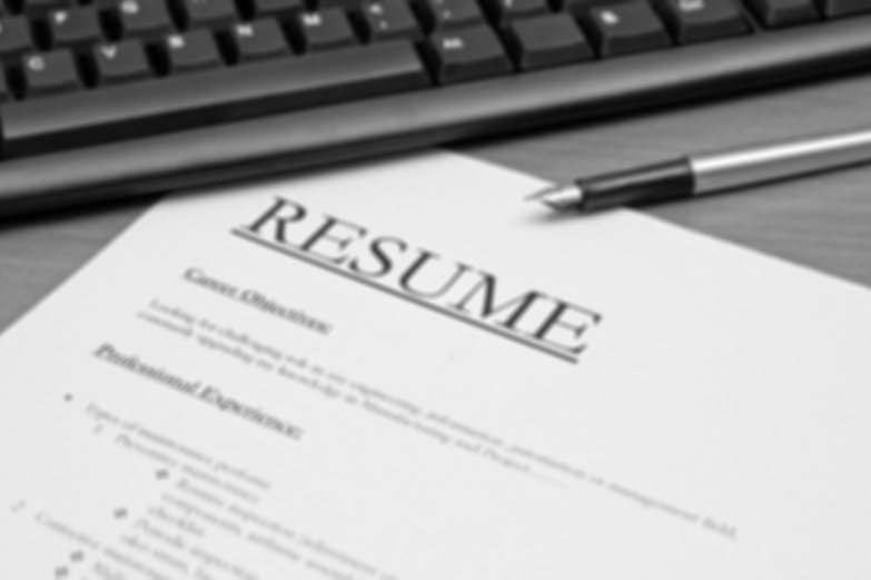Black and white image of a resume on a desk near a computer keyboard and a fountain pen