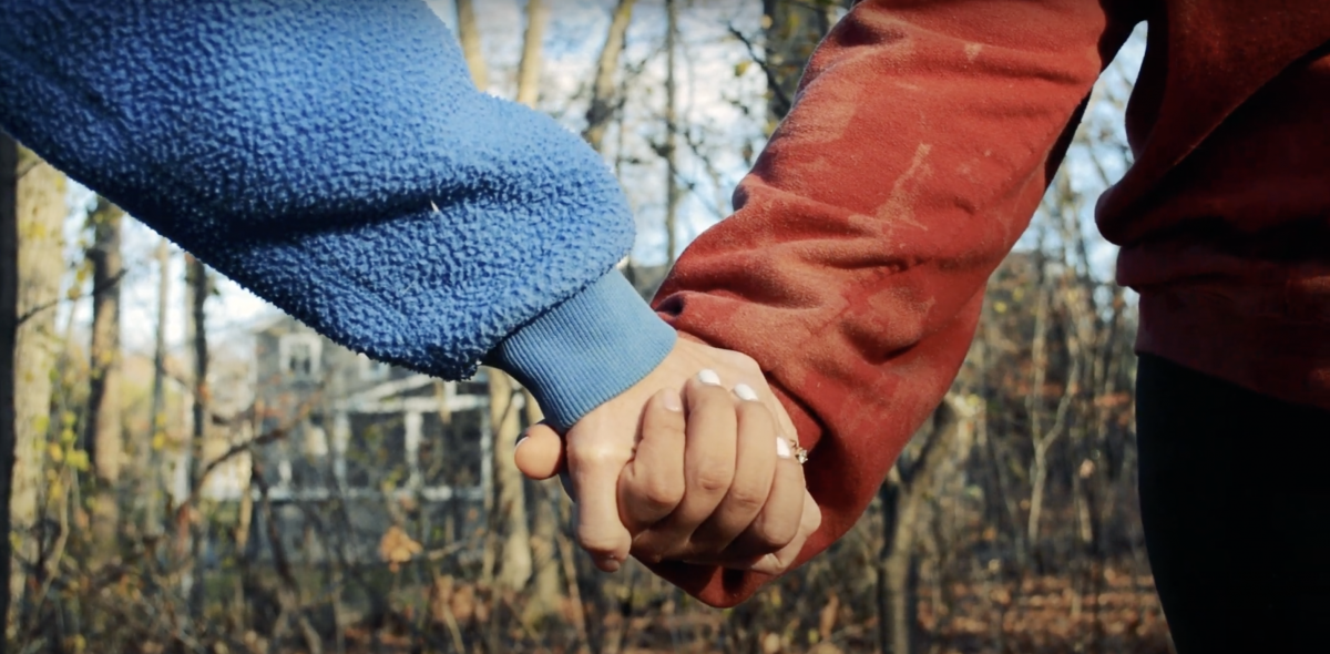 A closeup two people holding hands.