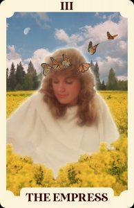 A tarot card with an image of a woman among flowers with butterflies near her head